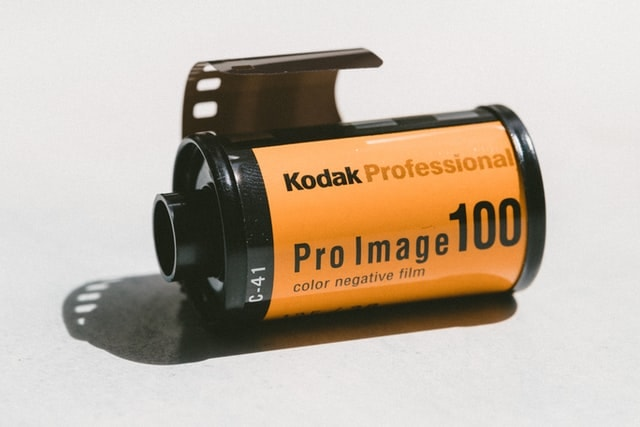 35mm color film canister with the film leader sticking out.