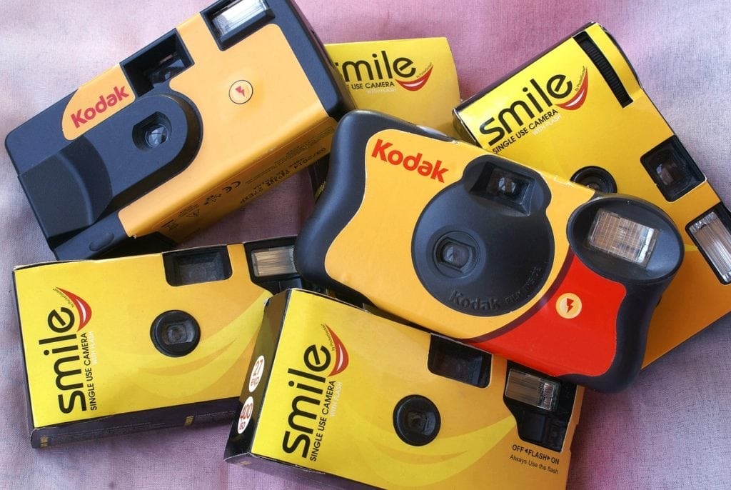 a pile of 6 disposable cameras