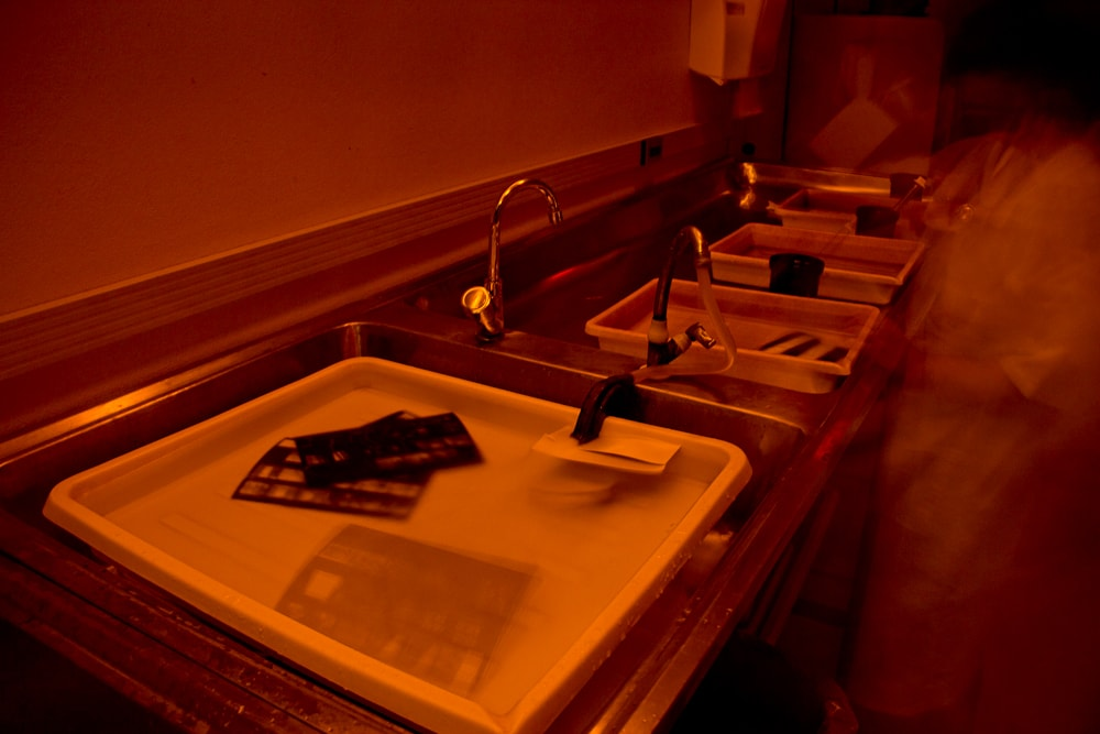 Processing prints in the darkroom using an amber light.