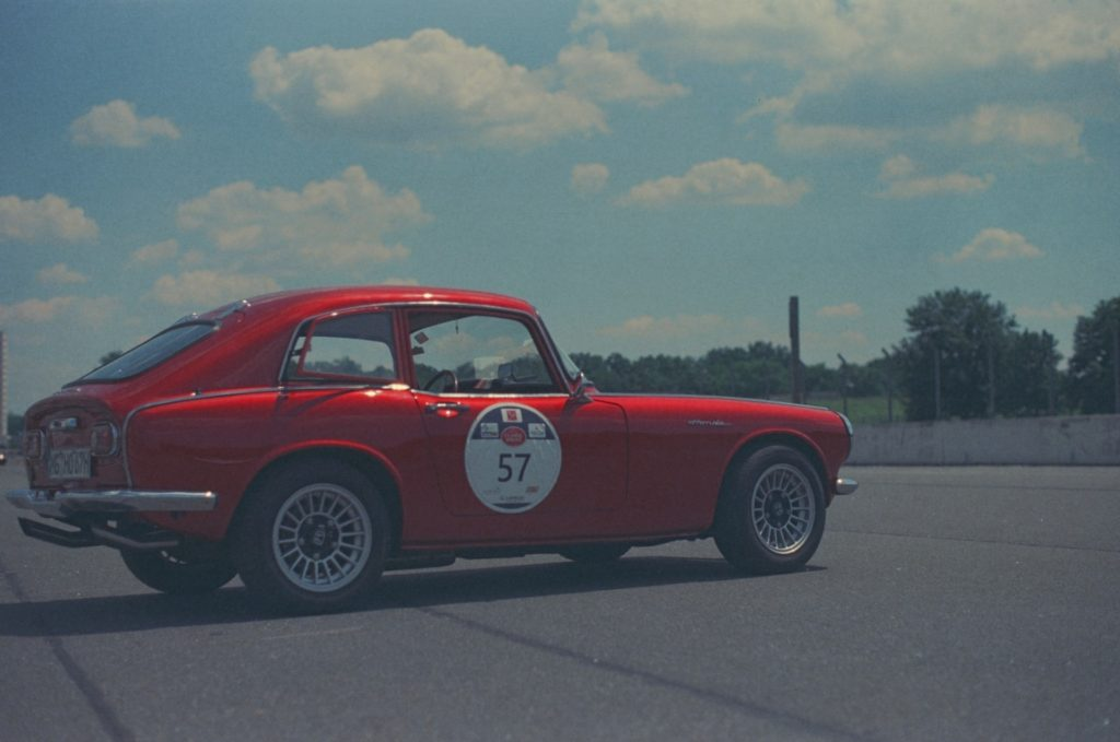 Image of a Red sports car on expired color film. You can see the limited contrast and dulling of the colors.