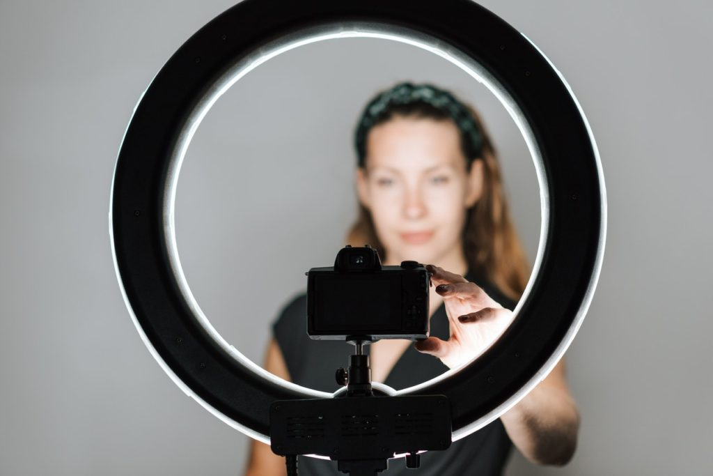 Woman taking a selfie using a camera on a tripod with a ring light.